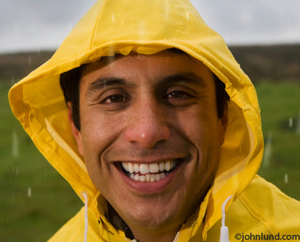 Happy smiling man wearing a yellow rain coat. The man has the yellow hood pulled over his head. The man is a good looking, even handsome, Latino,Mexican, or Hispanic man. A green field is the background. Close up of man in raincoats face.